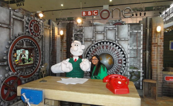 Becca posing with a human sized Wallacw seated at a wooden workbench with a red telephone on it