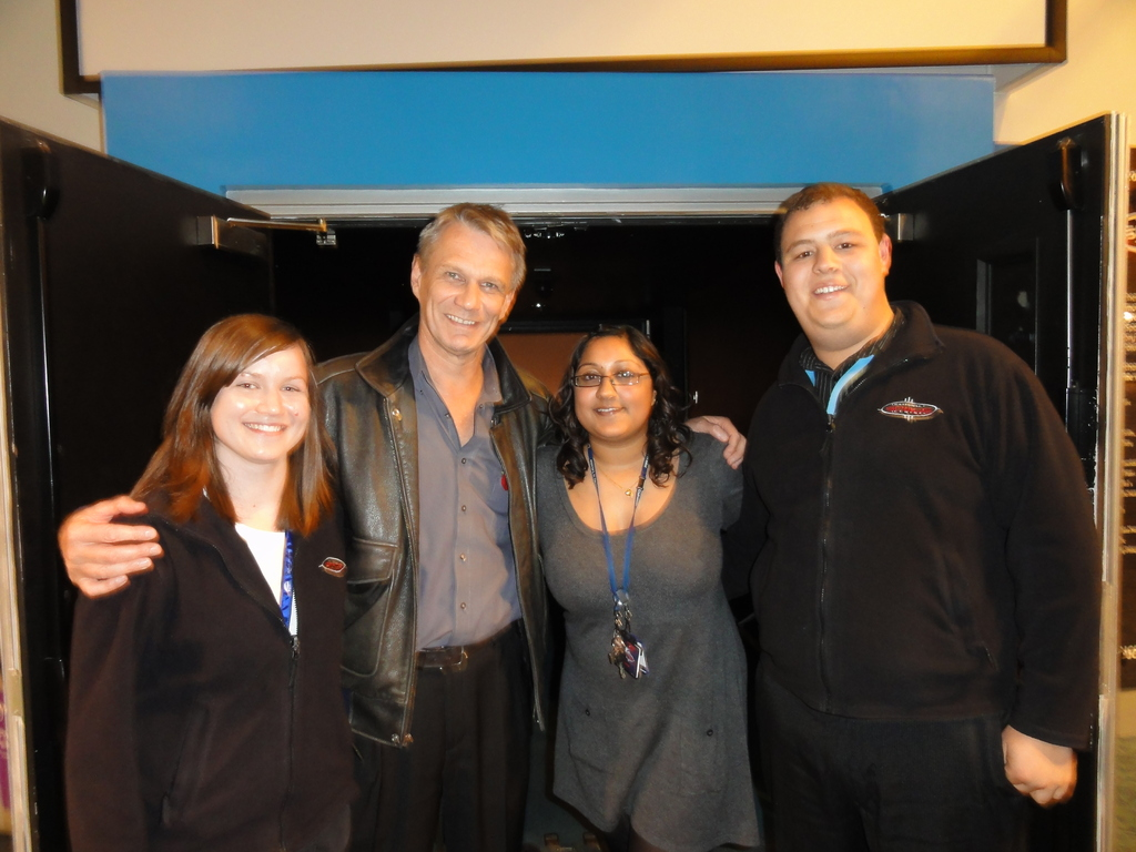 Becca and two colleagues posing with NASA astronaut Piers Sellers outside the NSC planetarium doors